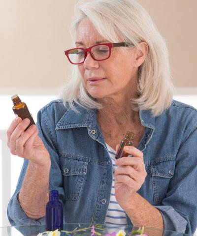 Woman looking at different essential oil bottles